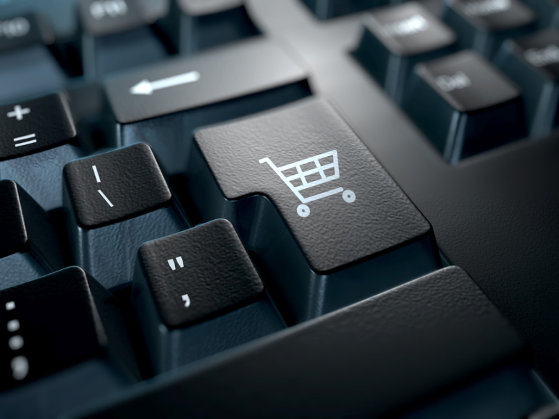 close-up of a keyboard with the enter key replaced with a shopping cart icon. E-commerce concept